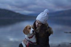 有她的狗的少女由湖 免版税库存照片