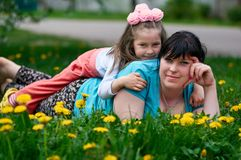 有婴孩的愉快的年轻母亲在蒲公英草甸享受夏时 免版税图库摄影