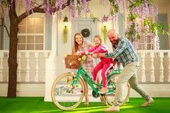 有孩子的愉快的父母,女儿,学会在家骑自行车,家庭生活方式暑假 图库摄影
