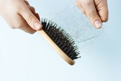 有宽松头发的梳子在蓝色背景在女性手上 库存图片