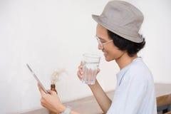 有帽子的年轻亚裔人和玻璃对片剂或膝上型计算机微笑,当拿着一杯水时 免版税图库摄影