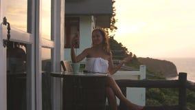 有年轻可爱的妇女视频聊天分享从旅馆阳台的陈列视图旅行经验在日落使用聪明 股票录像