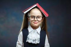 有开放书的逗人喜爱的女小学生呼喊盖子头 免版税库存照片