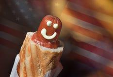 有微笑和番茄酱的一热狗在反对美国国旗的一个特写镜头 免版税库存图片
