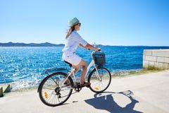 有城市自行车的少妇旅游骑自行车的人在海附近的镇 库存照片