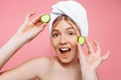 有在她的头附近被包裹的毛巾的可爱的快乐的妇女,拿着黄瓜切片在她的面孔附近,在桃红色背景 免版税库存图片