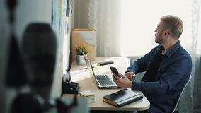 有在家运转黄色的头发的年轻有吸引力的商人戴着眼镜 使用坐在书桌的移动电话 股票录像