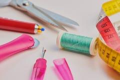 有剪刀和棉花螺纹的缝合的工具在白色背景 免版税库存图片
