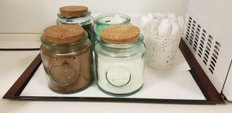 有咖啡茶和糖逗留的玻璃瓶子在桌上在箱子附近的办公室厨房里 免版税图库摄影