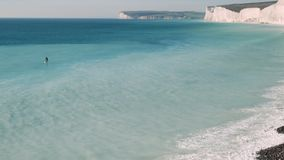 有桨划船的人在对岩石岸的一个冲浪板 影视素材