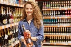 有棕色卷发的迷人的年轻女人,在牛仔布衣裳 拿着瓶酒精饮料,在超级市场架子附近的立场, 免版税图库摄影