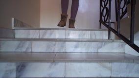 有棕色鞋子的一年轻女人沿着走大理石楼梯 影视素材