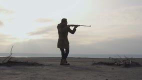 有步枪和被绘的面孔的年轻潜随猎物者人走在多云岗位apocatyptic荒原的 潜随猎物者-生存概念 股票录像