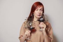 有毛皮海角的年轻滑稽的红发女孩斟酒服务员在白色背景举行和气味两块玻璃红酒 概念酒精中毒, 库存照片