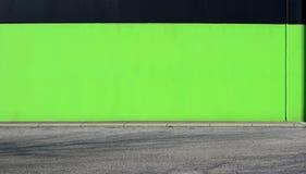 有水泥边路和一条柏油路的浅绿色和黑墙壁在前面 拷贝文本的背景 免版税库存图片