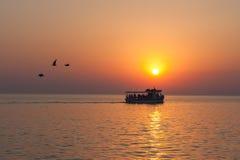 有游人的游艇与鸟飞行的日落的去 库存图片
