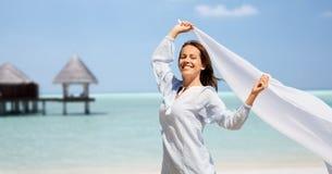 有挥动在海滩的风的披肩的愉快的妇女 图库摄影