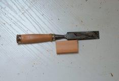 有木把柄的金属凿子在层压制品的背景 免版税库存照片