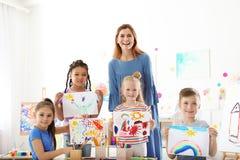 有显示他们的绘画的老师的逗人喜爱的小孩 免版税图库摄影