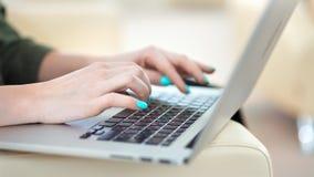 有明亮的五颜六色的修指甲键入的文本的特写镜头女性手在使用膝上型计算机个人计算机的键盘 影视素材