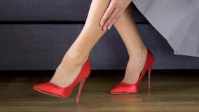 按摩在红色高跟鞋的美丽的性感的女商人痛苦的腿在工作以后 股票录像