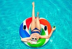 有放松在蓝色游泳场和饮料的可膨胀的圆环的美丽的年轻女人鸡尾酒 免版税库存图片