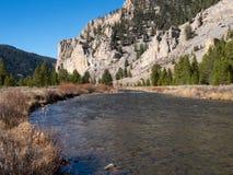 有秋天植被和岩石峭壁的重油河 免版税库存照片