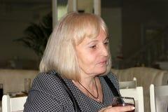 有突然移动理发的可爱的典雅的白肤金发的年长妇女,拿着一杯在多士的红酒,坐在桌上 免版税库存图片