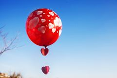 有红色气球的一女孩在天空蔚蓝 免版税库存图片