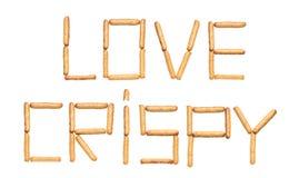 有罂粟种子的面包条组成的词爱酥脆在白色背景 库存图片