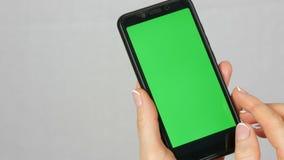 有美好的修指甲的穿着考究的整洁的女性手拿着有一把绿色屏幕或镀铬物钥匙的一个黑智能手机  股票录像