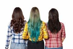 有美好的长发立场的三个年轻美女女孩在从后面的看法旁边 背景查出的白色 库存照片