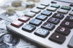 有美元和硬币的计算器在木背景 库存图片