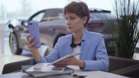 有短发的确信的妇女在经典蓝色正装坐在桌上谈话由手机使用前面照相机 股票视频