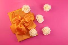 有玫瑰色花的礼物盒在桃红色背景 平的位置 库存照片