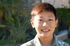 有牙括号的小孩亚裔男孩画象  免版税库存照片