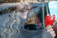 有白肤金发的卷发的年轻性感的妇女在汽车坐在冬天并且温暖她的在手取暖器的手作为心脏 免版税库存图片