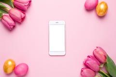 有白色屏幕、复活节彩蛋和花郁金香的手机在桃红色背景 库存图片