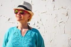 有白色在美好蓝色衬衣放松穿戴的帽子和桃红色太阳镜的年轻女人 免版税库存图片