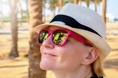 有白色放松在一好日子的帽子和桃红色太阳镜的少女 免版税库存照片