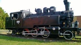 有白色轮子的蒸汽机车 在路轨的减速火箭的机车 黑色机车 免版税库存图片