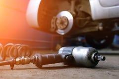 有电外面螺丝刀改变的轮胎的汽车机械师人 碗汽车推力增强的油替换服务 手替换在轮子的轮胎 轮胎设施 免版税图库摄影