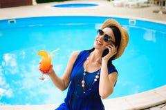 有电话的美丽的年轻女人在游泳场附近 免版税图库摄影