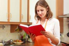 有菜谱的主妇在厨房里 库存图片