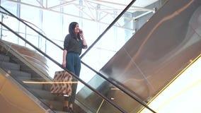 有袋子的年轻愉快的妇女谈话在电话,当站立在自动扶梯在购物中心时 影视素材