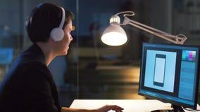 有计算机的图表设计师在夜办公室 股票录像