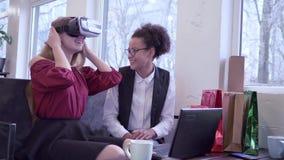 有计算机膝上型计算机和白种人女朋友的快乐的深色皮肤的少女到VR在真正的耳机戏剧里 股票视频
