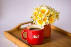 有词的'爱'一个红色杯子用热的咖啡/茶和雏菊花束在一个木盘子的 库存图片