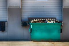 有车库门和大型垃圾桶的仓库外墙 免版税图库摄影