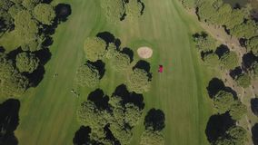 有运转在高尔夫球场的贷款刈草机的一台拖拉机 股票录像